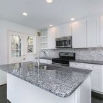 a kitchen island with granite and white cabinets