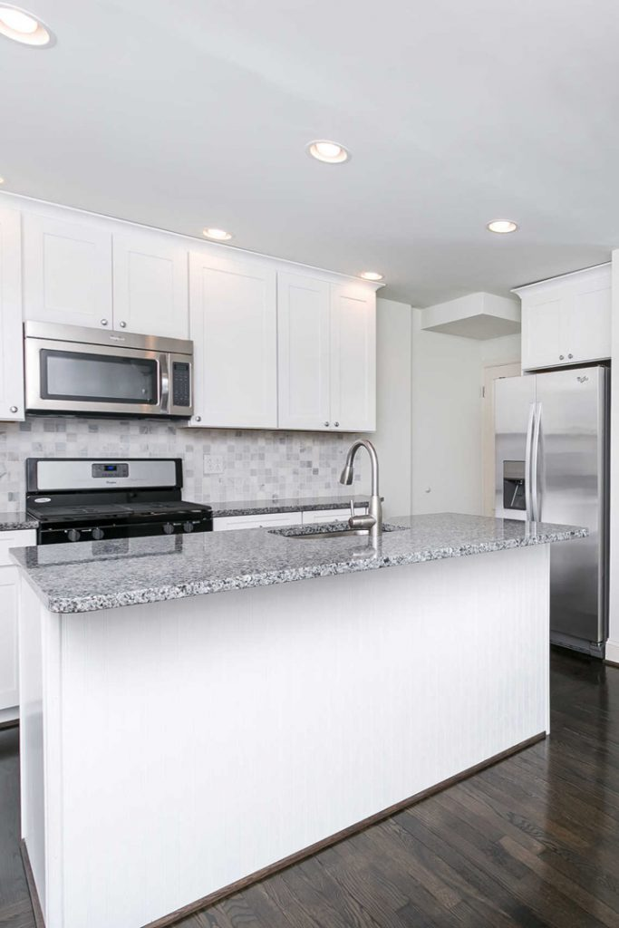 a white kitchen with stainless steel appliances and stone counters