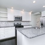 a kitchen with granite counters and white cabinets