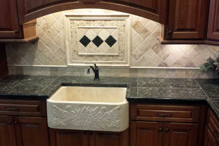 a stone counter top and tiled wall with custom sink