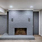 a grey cinder block fireplace with carpet and white walls