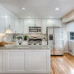 a kitchen with granite countertops white cabinets and wood floor