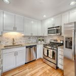 a refurbished kitchen with wooden floors, stainless steel appliances and white cabinets